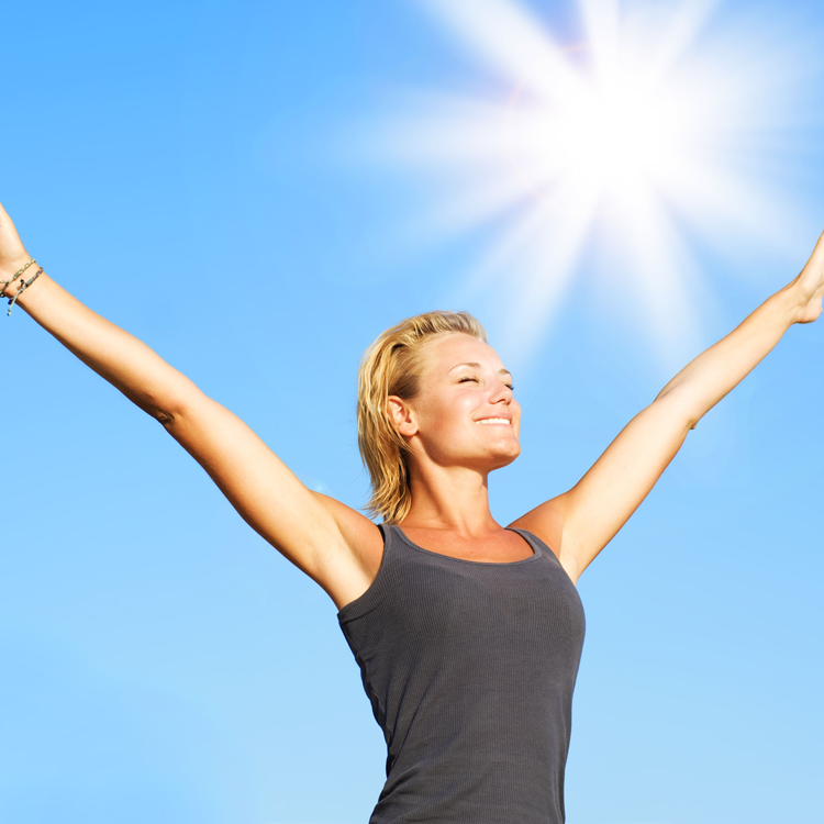 a woman standing in the sun while smiling and holding her hands up