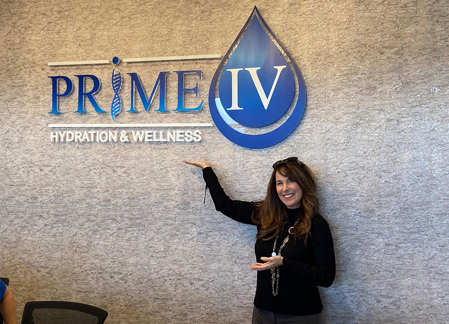 Prime IV founder pointing to a Prime IV wall sign